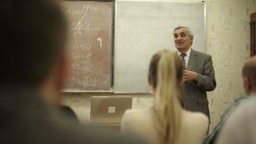 El grupo de estudiantes en una sala de clase, escuchando como su profesor lleva a cabo una conferencia almacen de video