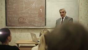 El grupo de estudiantes en una sala de clase, escuchando como su profesor lleva a cabo una conferencia almacen de metraje de vídeo