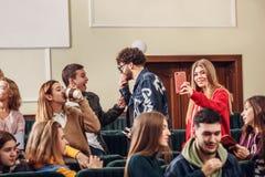 El grupo de estudiantes felices alegres que se sientan en una sala de conferencias antes de la lección foto de archivo