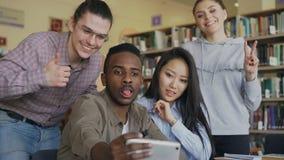 El grupo de estudiantes internacionales se divierte que sonríen y que hacen las fotos del selfie en cámara del smartphone en la b almacen de metraje de vídeo
