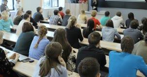 El grupo de estudiantes universitarios que se sientan en sus escritorios en auditorio y que escuchan como su profesor lleva a cab