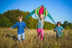 El grupo de feliz y de sonrisa embroma el playingin con la cometa al aire libre Imagen de archivo libre de regalías