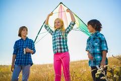 El grupo de feliz y de sonrisa embroma el playingin con la cometa al aire libre Fotografía de archivo
