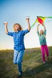 El grupo de feliz y de sonrisa embroma el playingin con la cometa al aire libre Imágenes de archivo libres de regalías