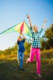 El grupo de feliz y de sonrisa embroma el playingin con la cometa al aire libre Foto de archivo