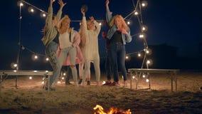 El grupo de gente del baile que canta y se divierte cerca de hoguera en la playa en la iluminación de guirnaldas almacen de video