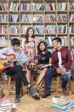 El grupo de gente feliz que juega música y canta la canción en sitio de la biblioteca Imagenes de archivo