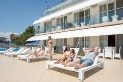 El grupo de gente feliz y joven es relajante y que disfruta de verano en un fondo del hotel de lujo Gente joven en Imagen de archivo