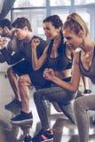 El grupo de gente joven atlética en la ropa de deportes que hace estocada ejercita en el gimnasio fotografía de archivo libre de regalías