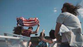 El grupo de gente joven aumenta la bandera americana almacen de video