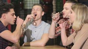 El grupo de gente joven bebe del licor en el restaurante almacen de metraje de vídeo