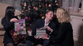 El grupo de gente joven da presentes el uno al otro debajo del árbol en la Navidad interior, celebración del Año Nuevo metrajes