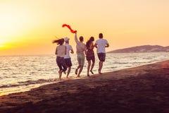 El grupo de gente joven feliz está corriendo en el fondo de la playa y del mar de la puesta del sol Imagen de archivo libre de regalías