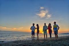 El grupo de gente joven feliz está corriendo en el fondo de la playa y del mar de la puesta del sol Imágenes de archivo libres de regalías