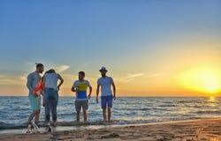El grupo de gente joven feliz está corriendo en el fondo de la playa y del mar de la puesta del sol Fotografía de archivo libre de regalías