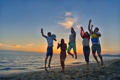 El grupo de gente joven feliz está corriendo en el fondo de la playa y del mar de la puesta del sol Fotografía de archivo