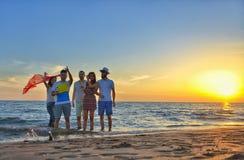 El grupo de gente joven feliz está corriendo en el fondo de la playa y del mar de la puesta del sol Fotos de archivo libres de regalías