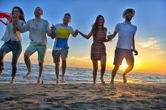 El grupo de gente joven feliz está corriendo en el fondo de la playa y del mar de la puesta del sol Foto de archivo libre de regalías