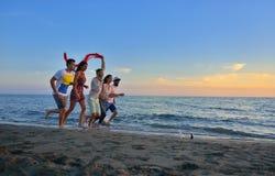 El grupo de gente joven feliz está corriendo en el fondo de la playa y del mar de la puesta del sol Fotos de archivo