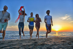 El grupo de gente joven feliz está corriendo en el fondo de la playa y del mar de la puesta del sol Foto de archivo