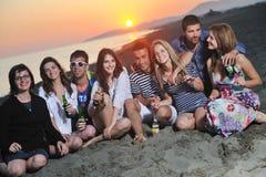 El grupo de gente joven goza en la playa Imagen de archivo libre de regalías