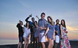 El grupo de gente joven goza en la playa Imágenes de archivo libres de regalías