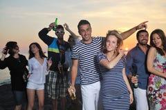 El grupo de gente joven goza en la playa Fotografía de archivo