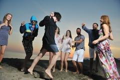 El grupo de gente joven goza en la playa Foto de archivo