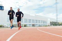 El grupo de gente joven que corre en la pista coloca Imagen de archivo libre de regalías