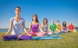 El grupo de gente joven tiene meditación en clase de la yoga. foto de archivo