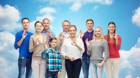 El grupo de gente sonriente que muestra la mano aceptable firma Imágenes de archivo libres de regalías
