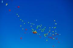 El grupo de helio multicolor llenó los globos en el cielo Foto de archivo