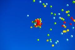 El grupo de helio multicolor llenó los globos en el cielo Imagenes de archivo