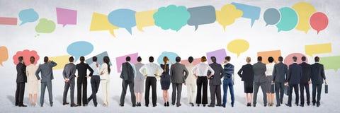 El grupo de hombres de negocios que se colocan delante de charla colorida burbujea imagenes de archivo