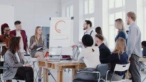 El grupo de hombres de negocios jovenes escucha el jefe joven que habla en la reunión ligera moderna de la oficina del desván, EP almacen de video