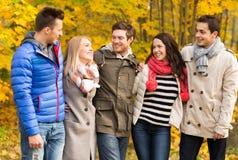 El grupo de hombres sonrientes y las mujeres en otoño parquean Imagenes de archivo