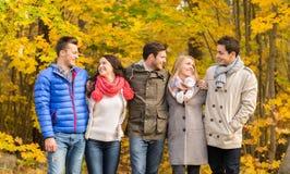 El grupo de hombres sonrientes y las mujeres en otoño parquean Foto de archivo libre de regalías