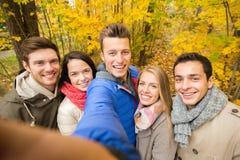 El grupo de hombres sonrientes y las mujeres en otoño parquean Fotos de archivo libres de regalías