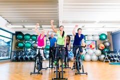 El grupo de hombres y de mujeres que hacen girar en aptitud bikes en gimnasio imagen de archivo