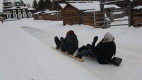 El grupo de individuos felices rueda abajo de la colina helada en el esquí de madera metrajes