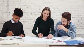 El grupo de interioristas jovenes combina el trabajo junto en oficina creativa Profesionales jovenes que hacen sentarse de los bo metrajes