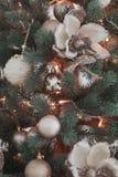 El grupo de juguetes de la Navidad del vintage de la plata y del oro pesa en el primer del árbol de navidad de las ramas del verd Foto de archivo