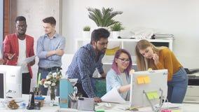 El grupo de la gente joven en oficina moderna tiene discusi?n de un nuevo proyecto metrajes