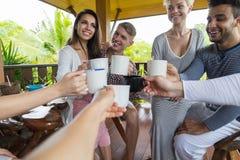 El grupo de la gente joven que desayuna en el hotel tropical de la terraza, tintineo de los amigos ahueca vacaciones tropicales d imágenes de archivo libres de regalías