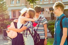 El grupo de los adolescentes felices 13, 14 años caminando a lo largo de la calle de la ciudad, los amigos se saluda en una reuni Imágenes de archivo libres de regalías