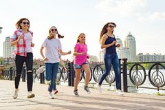 El grupo de madres y las hijas están corriendo a lo largo del camino en el parque Fotografía de archivo