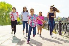 El grupo de madres y las hijas están corriendo a lo largo del camino en el parque Antecedentes urbanos Fotos de archivo