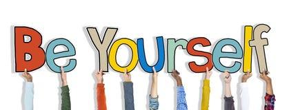 El grupo de manos que llevan a cabo la palabra sea usted mismo Imágenes de archivo libres de regalías