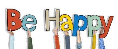 El grupo de manos que llevan a cabo palabra sea feliz Fotografía de archivo libre de regalías