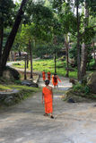 El grupo de monjes budistas asiáticos surorientales jovenes camina en parque del templo Foto de archivo libre de regalías